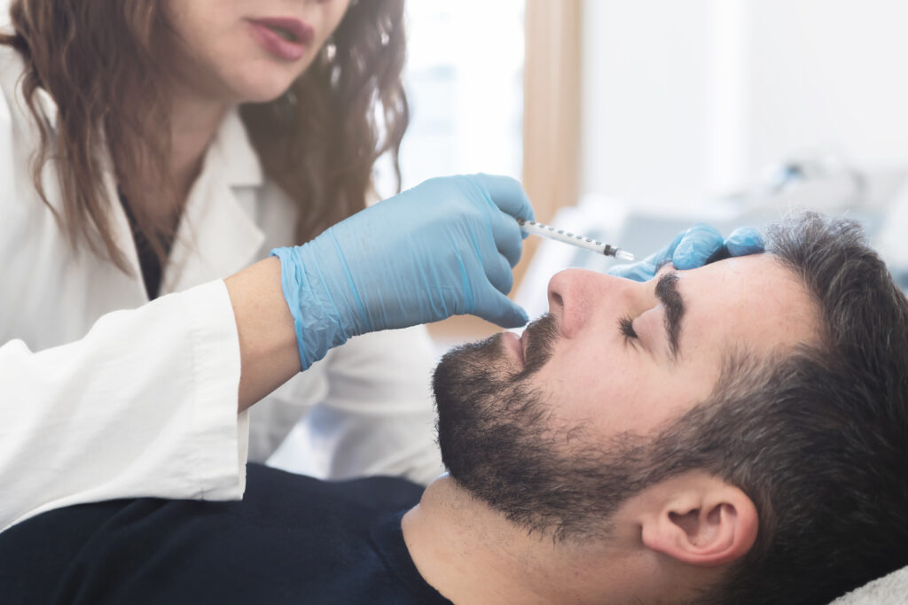 Female doctor putting fillers in man's forehead at Restorative Health